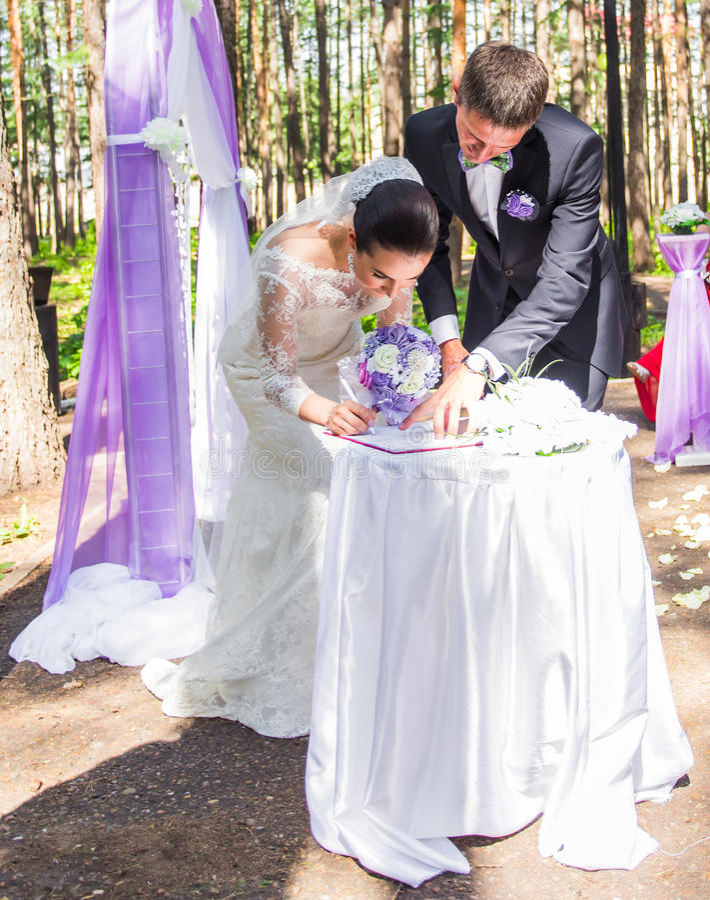 Novia y novio que dejan sus firmas en ceremonia de boda fotos de archivo