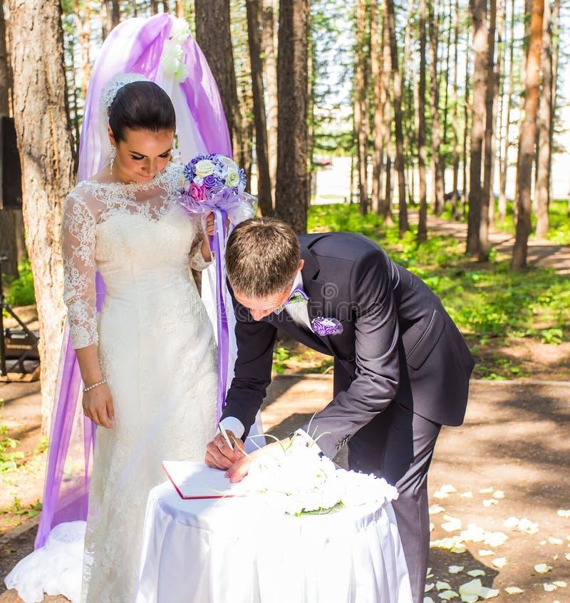 Novia y novio que dejan sus firmas en ceremonia de boda fotografía de archivo
