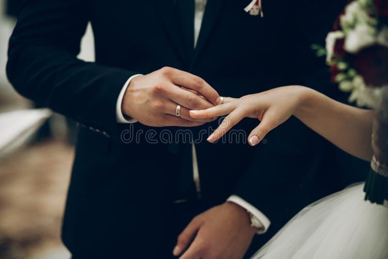 Novia y novio que intercambian los anillos de bodas, poniendo en dur de los fingeres fotos de archivo