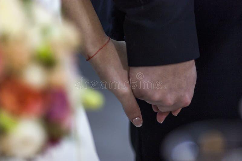 Novia y novio que llevan a cabo las manos durante una ceremonia del fondo del ramo nupcial borroso efecto del grano amantes de la foto de archivo