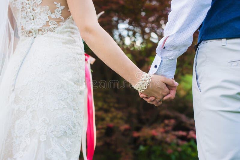 Novia y novio que llevan a cabo las manos, primer imagen de archivo libre de regalías