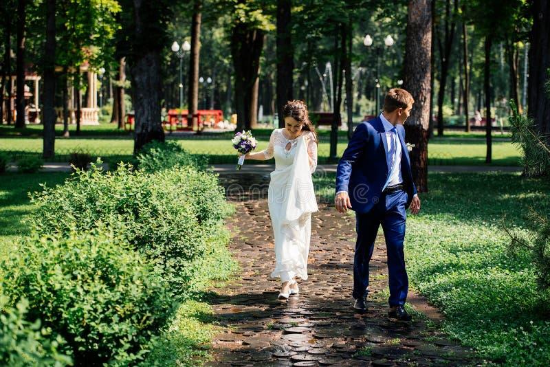 Novia y novio que recorren en el parque Pares en amor en el día de boda imagen de archivo libre de regalías