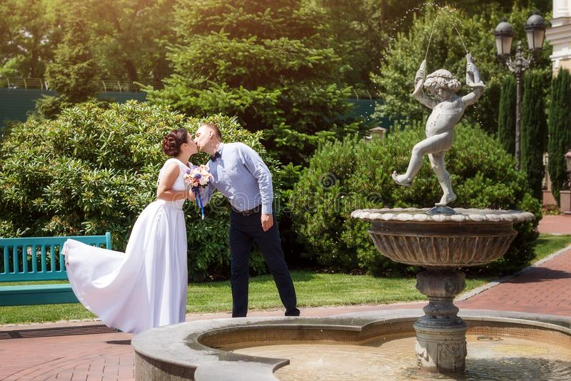 Novia y novio que se besan al aire libre Día de boda de pares, de mujer feliz del recién casado y de hombre nupciales abrazando c fotografía de archivo
