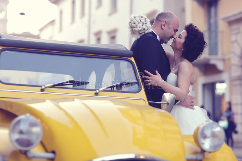 Novia y novio que se besan cerca del coche amarillo fotografía de archivo libre de regalías