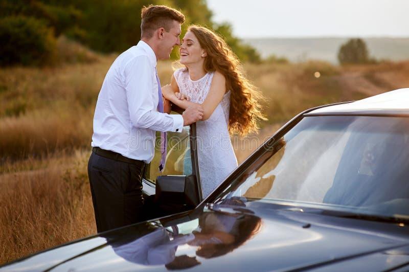 Novia y novio que se besan cerca del coche en paseo de la boda fotos de archivo libres de regalías
