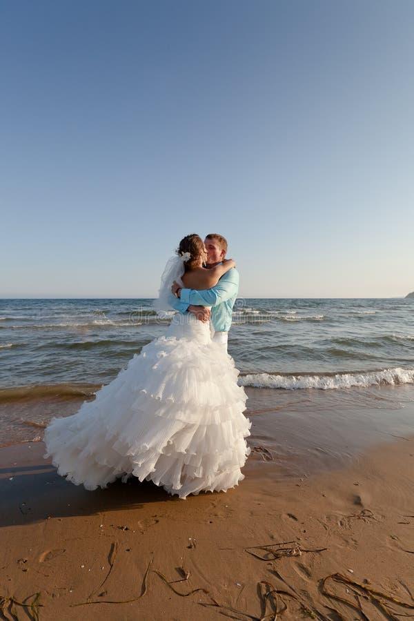 Novia y novio que se besan en la playa fotos de archivo libres de regalías