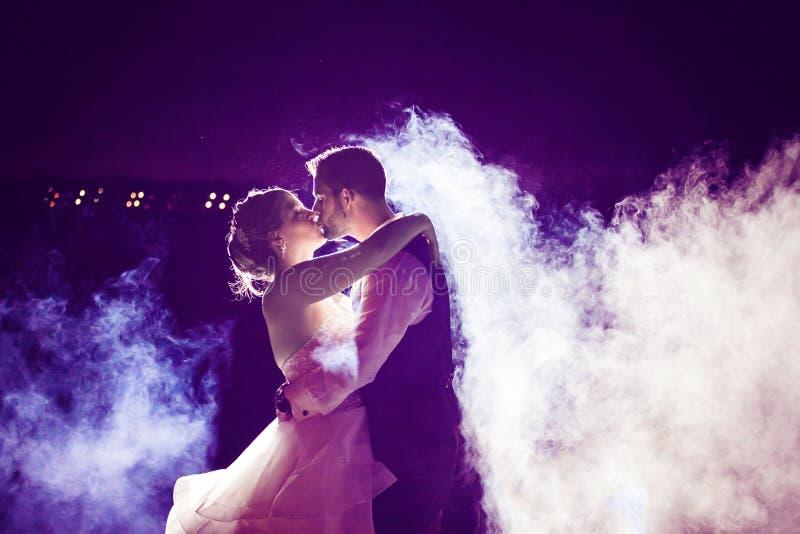 Novia y novio que se besan en niebla con el cielo nocturno púrpura imagen de archivo