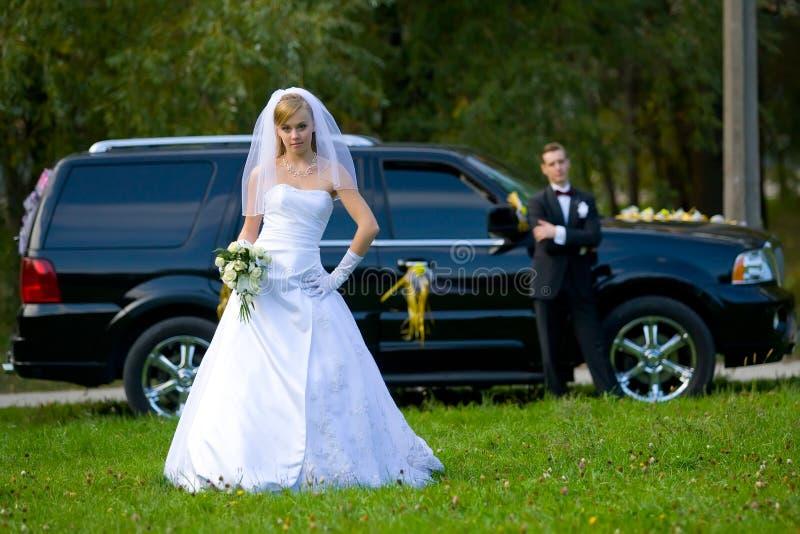 Novia y novio que se colocan delante del coche de la boda imagen de archivo libre de regalías