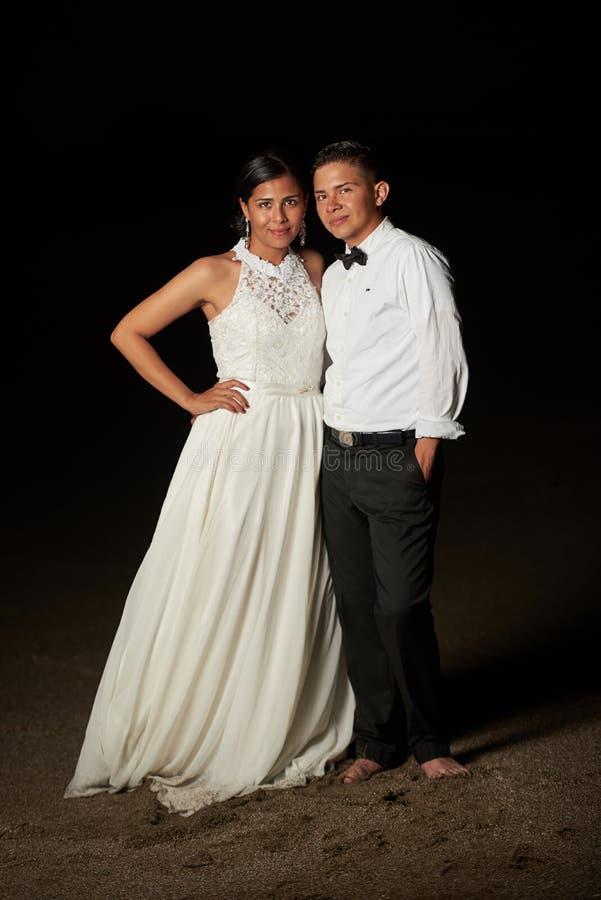 Novia y novio que se colocan en la arena de la playa foto de archivo libre de regalías