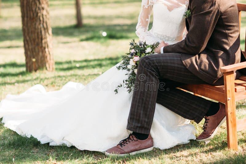 Novia y novio que se sientan en banco en parque imagenes de archivo