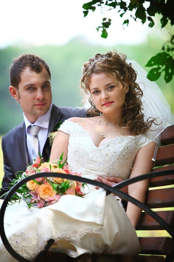 Novia y novio que se sientan en el banco fotos de archivo