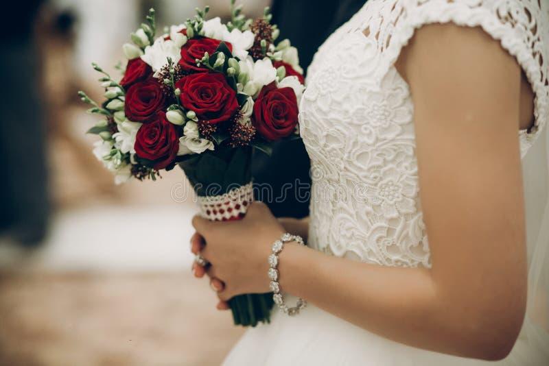 Novia y novio que sostienen el ramo elegante de rosas rojas antes de wedd imagen de archivo libre de regalías