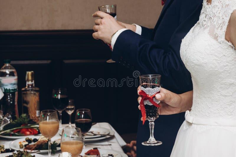 Novia y novio que tuestan con champán en la recepción nupcial adentro fotos de archivo