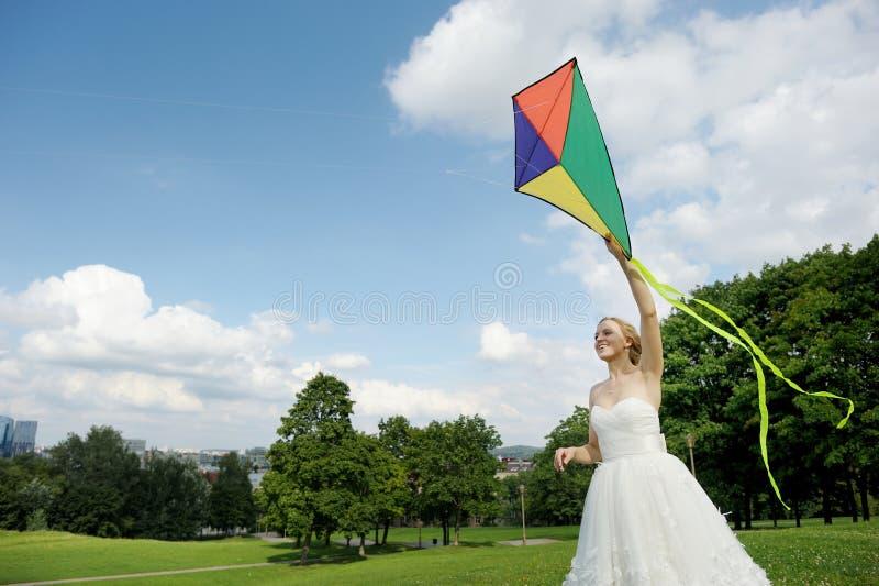 Novia y novio que vuelan una cometa en un día de boda imagenes de archivo