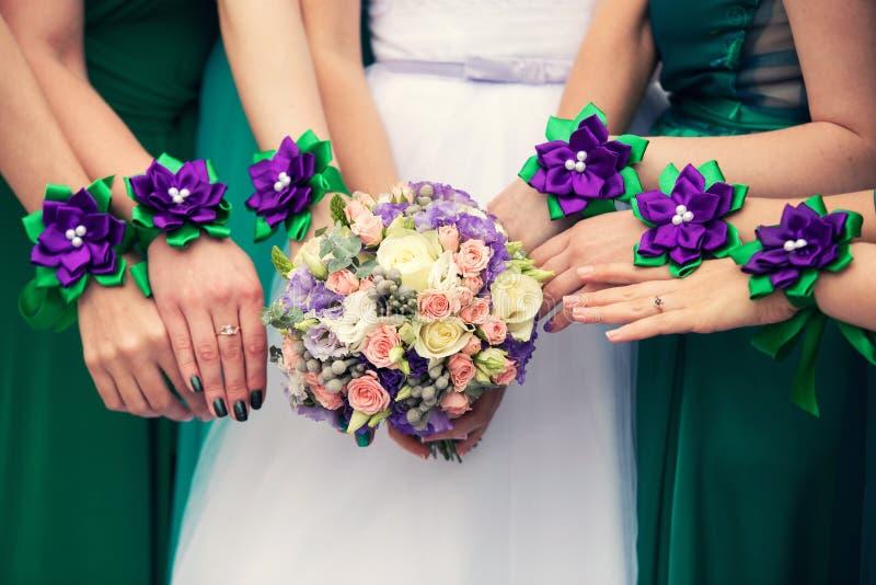 Novia y sus damas de honor con las pulseras en las manos imagen de archivo