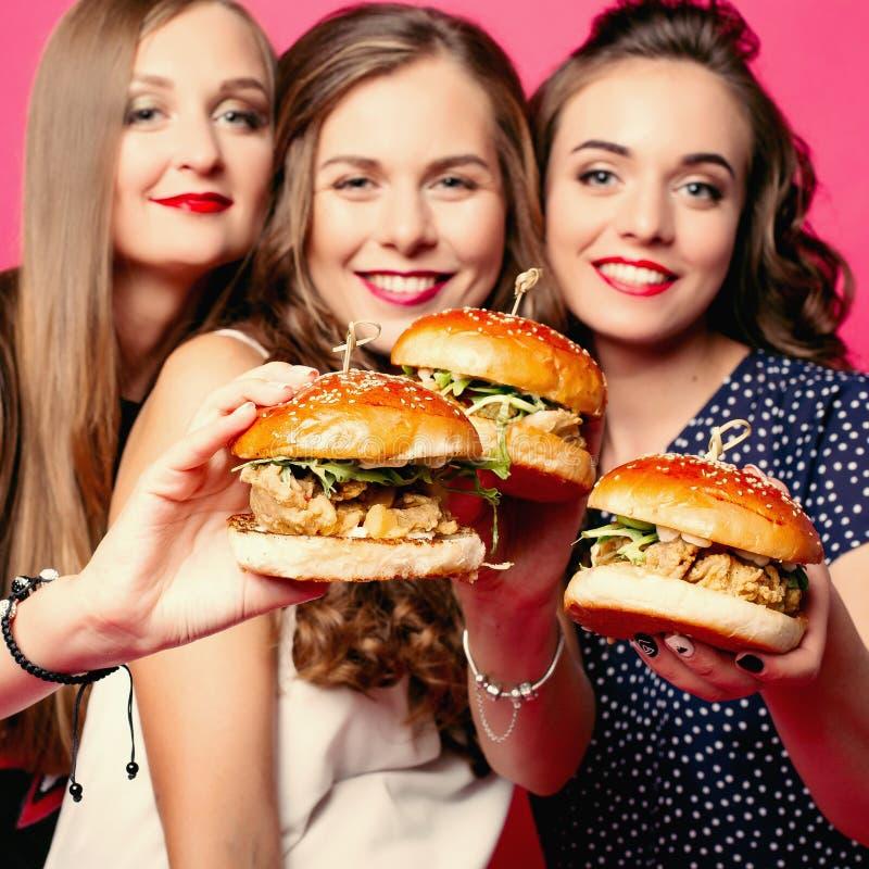 Novias bonitas con las hamburguesas jugosas imagenes de archivo