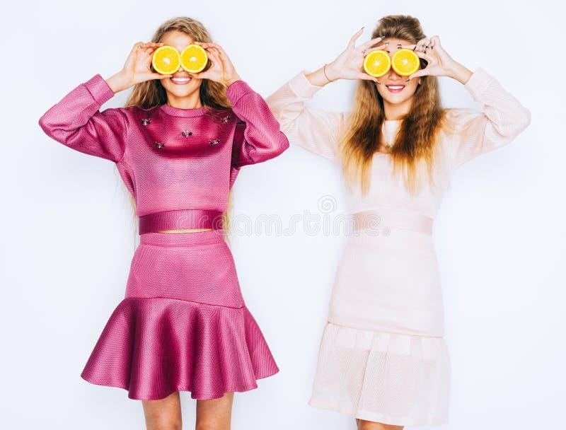 Novias divertidas hermosas jovenes de la moda con la rebanada anaranjada en el fondo blanco Maquillaje y peinado Diviértase y eng fotos de archivo