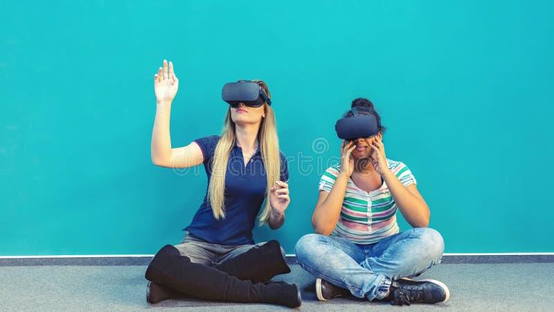 Novias felices que juegan sobre los vidrios del vr interiores foto de archivo
