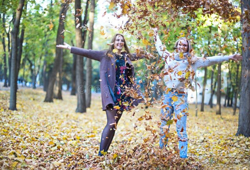 Novias jovenes hermosas de moda que caminan junto en el fondo del parque del oto?o Divertirse y presentaci?n fotos de archivo