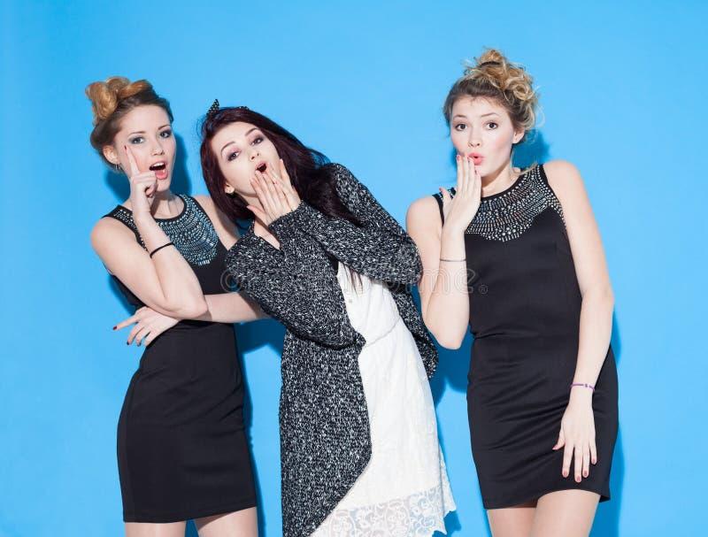 Novias jovenes hermosas de moda que se unen cerca de un fondo azul Dos blondes y una morenita Tener divertido y posición imagenes de archivo