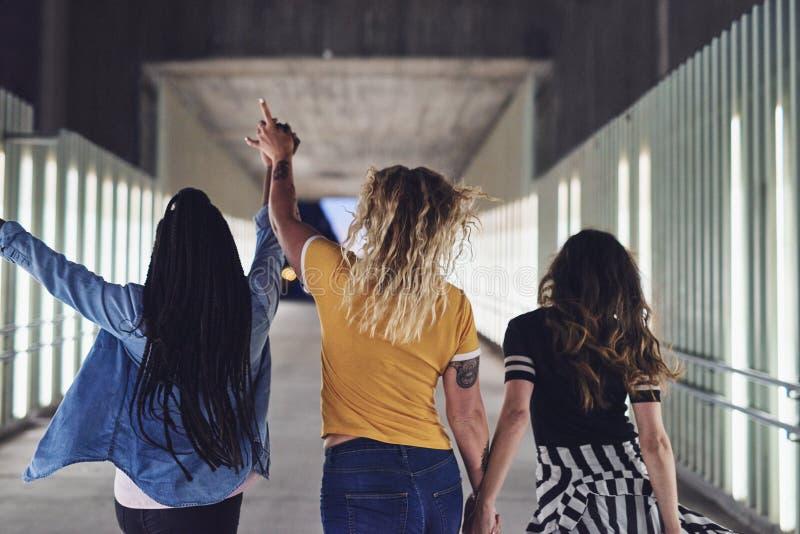 Novias jovenes que llevan a cabo las manos juntas en la ciudad en la noche foto de archivo libre de regalías