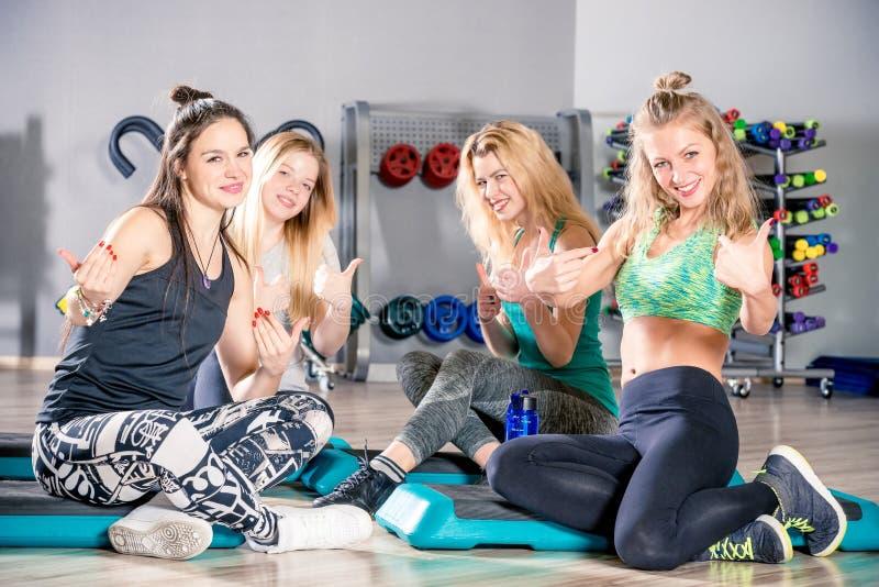 Novias lindas felices después de entrenar en la sentada del gimnasio fotografía de archivo