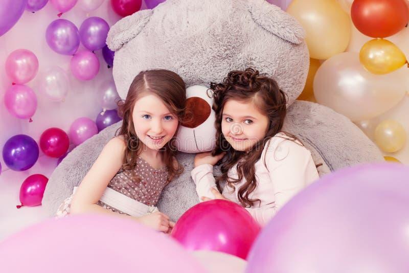 Novias preciosas que presentan con el oso de peluche grande fotos de archivo
