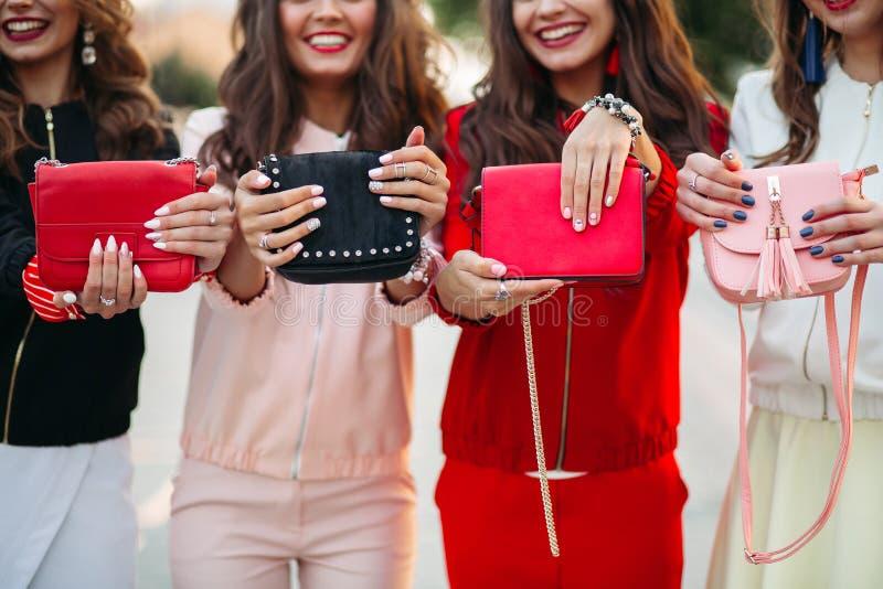 Novias sonrientes con la manicura que sostiene los bolsos fotos de archivo