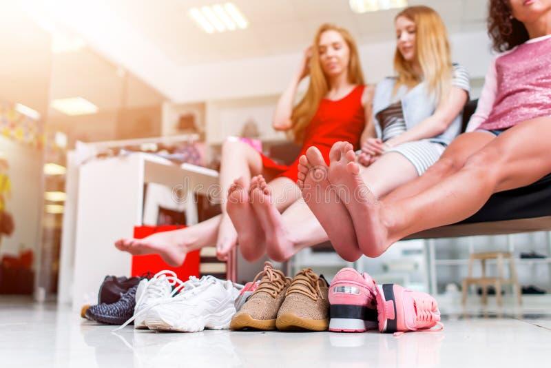 Novias sonrientes jovenes que se sientan en una tienda de ropa que mira sus pies desnudos y pila de nuevos zapatos y de risa imagen de archivo libre de regalías