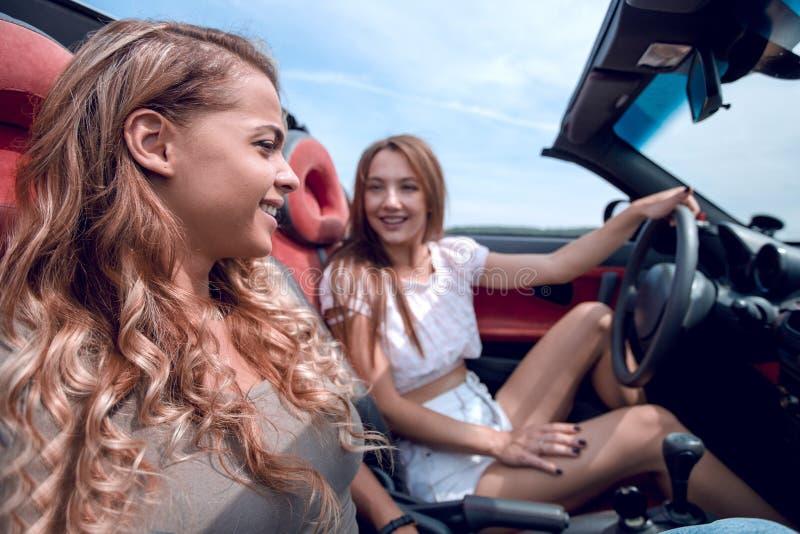 Novias sonrientes que viajan en un coche convertible fotos de archivo libres de regalías