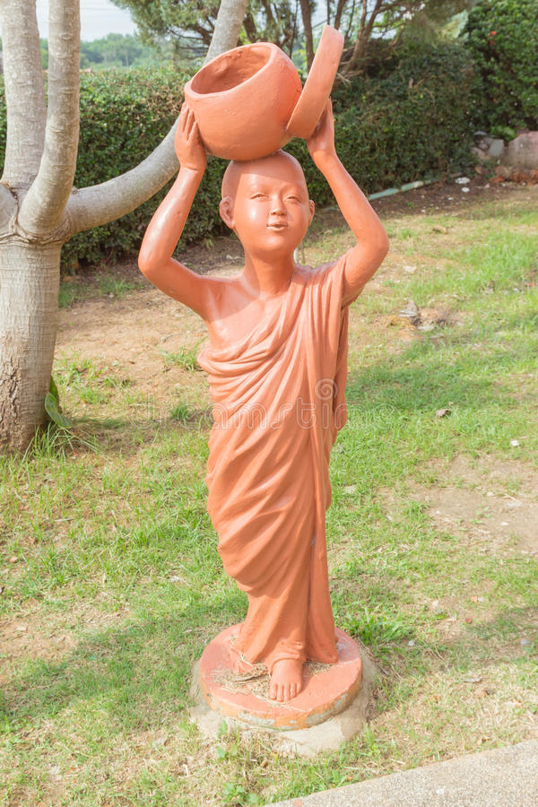 Novice bouddhiste tenant la poupée d'argile de cuvette d'aumône au tem bouddhiste thaïlandais image libre de droits