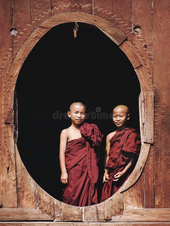 Novice Buddhist Monks at Shwe Yan Pyay Monastery, Nyaung Shwe, Myanmar. Novice Buddhist monks standing by the window at Shwe Yan Pyay Monastery in Nyaung Shwe stock photography