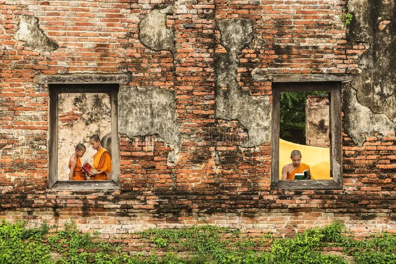 Novice monk reading books in ruins. royalty free stock image