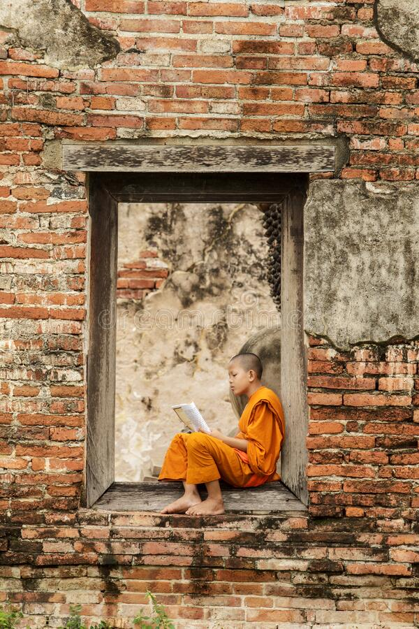 Novice monk reading books in ruins at Putthaisawan temple. Novice monk reading books in ruins at Putthaisawan temple in Ayutthaya, Thailand royalty free stock photo