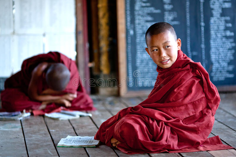 Novice monks, Myanmar. NYAUNG SHWE, MYANMAR - JANUARY 16: Novice monks learning together in class room of in the Shwe Yan Pyay monastery before they head out on stock photography