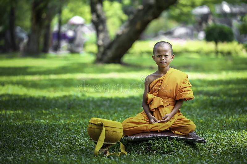 A novice sitting on a green lawn. BANGKOK, THAILAND – APRIL 8: A small summer novice who is meditating on the outdoor with green nature royalty free stock image