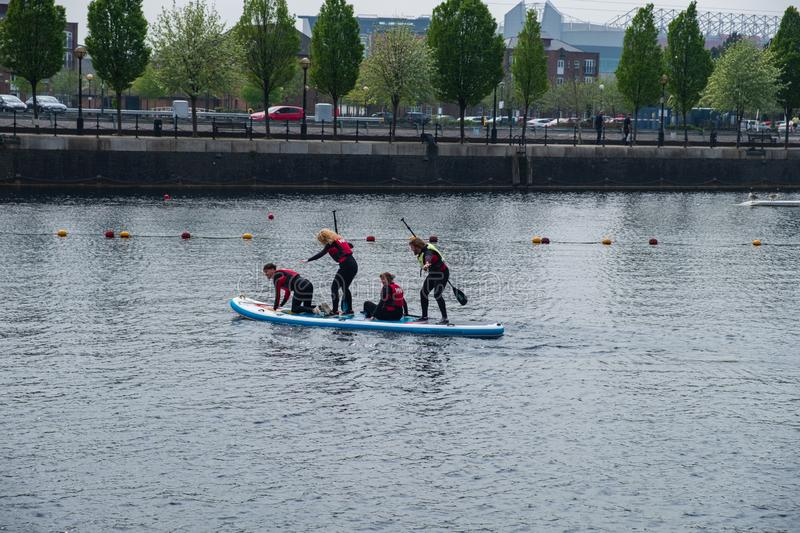 Novice students learn stand up paddle boarding at Salford Quays in Manchester, UK. Manchester, United Kingdom - April 24, 2019: Novice students learn stand up stock photography