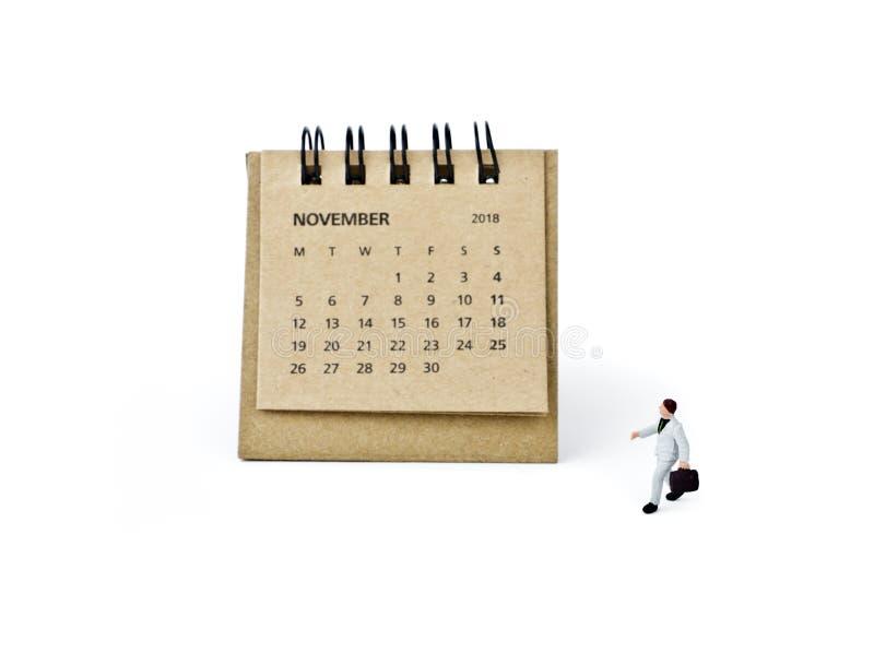 noviembre Haga calendarios la hoja y al hombre de negocios plástico miniatura en wh foto de archivo