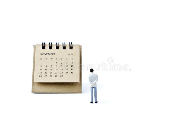 noviembre Haga calendarios la hoja y al hombre plástico miniatura en la parte posterior del blanco imagenes de archivo