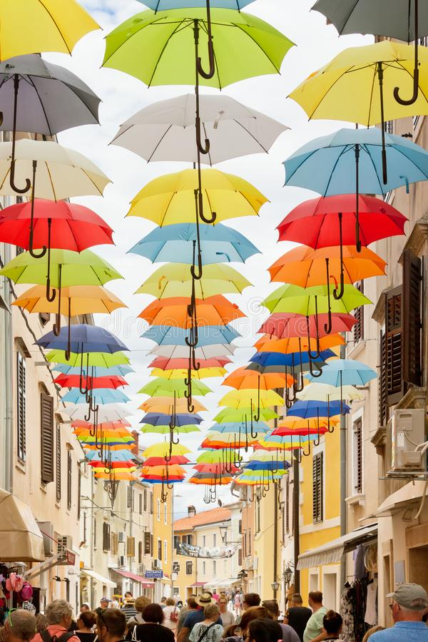 Novigrad, Istria, Croatia - SEPTEMBER 3, 2017 - Tourists walking through an alleyway with colorful umbrellas above royalty free stock images