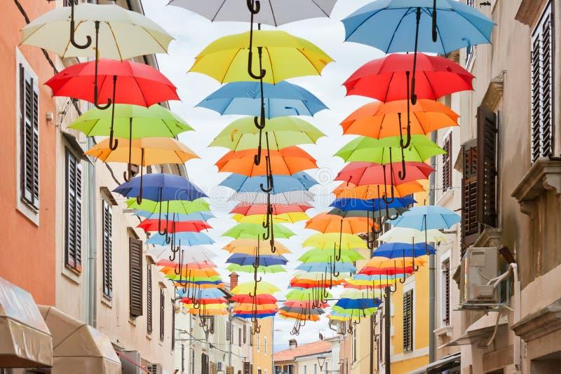 Novigrad, Istria, Croazia - ombrelli variopinti pittoreschi nei vicoli di Novigrad fotografie stock