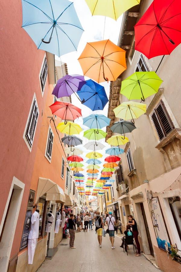 Novigrad Istria, Kroatien - SEPTEMBER 3, 2017 - turister som går till och med den gamla staden av Novigrad med paraplyer ovanför  arkivbilder