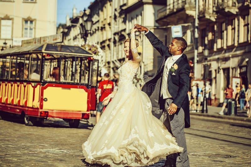Novio afroamericano feliz y baile lindo de la novia en la calle fotografía de archivo libre de regalías