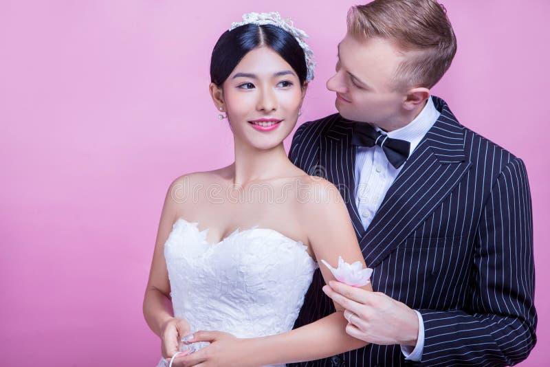 Novio cariñoso que sostiene la flor mientras que mira a la novia contra fondo rosado foto de archivo