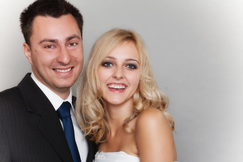 Novio casado feliz de la novia de la pareja en fondo gris foto de archivo libre de regalías