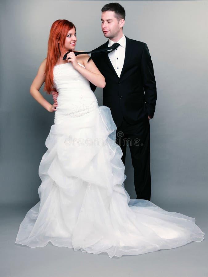 Novio casado feliz de la novia de la pareja en fondo gris imagenes de archivo