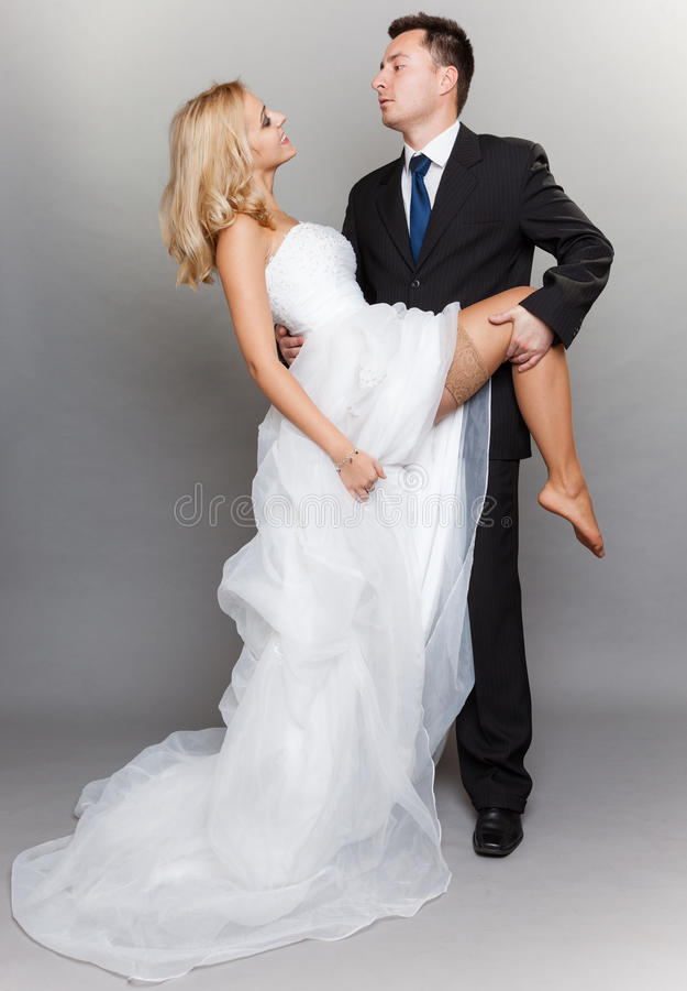 Novio casado feliz de la novia de la pareja en fondo gris imagen de archivo