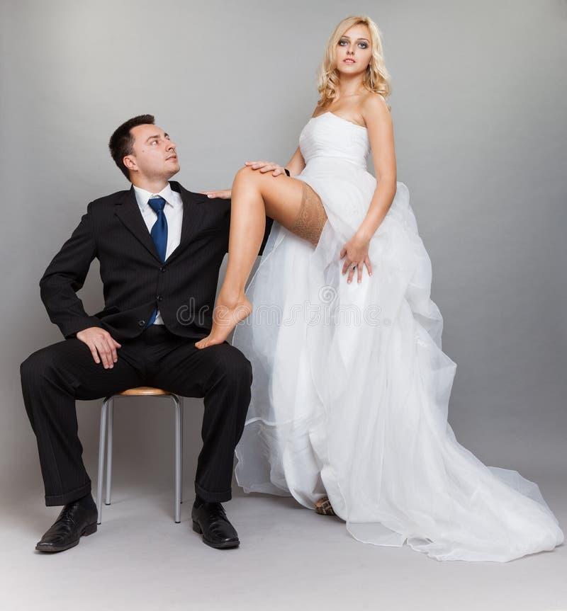 Novio casado feliz de la novia de la pareja en fondo gris imagen de archivo libre de regalías