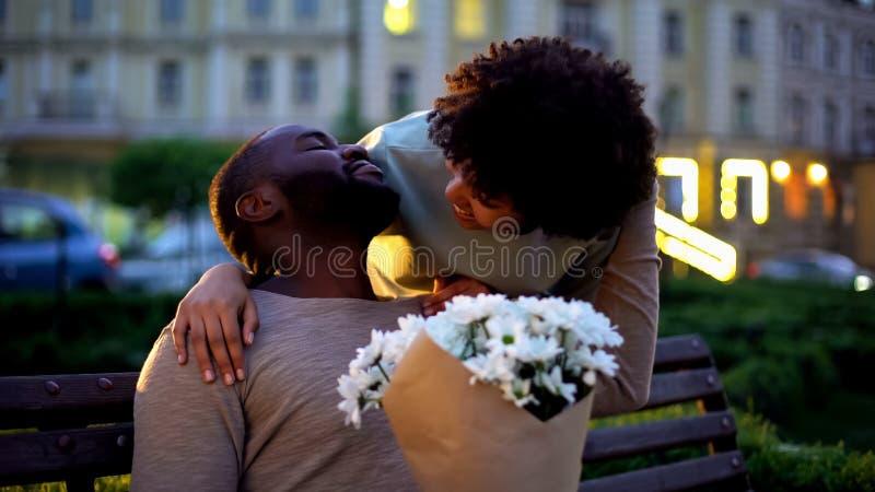 Novio de abarcamiento de la señora, mirando con el amor, sosteniendo las flores, fecha romántica imagen de archivo libre de regalías