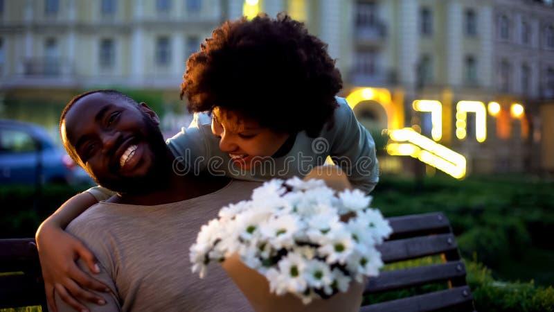 Novio de abrazo femenino, mirando con el amor, sosteniendo las flores, fecha romántica foto de archivo